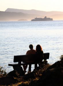 Couple gazes at ferry at Roesland, Pender Island BC