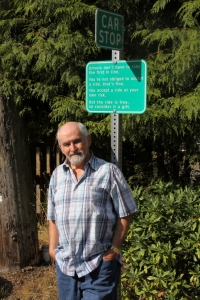 Barry Mathias at car stop sign, Pender Island BC